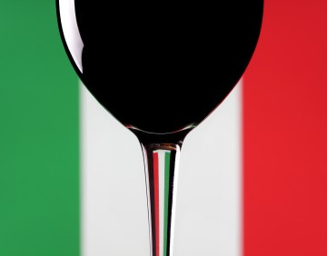 A glass of red wine on an Italian flag background.
